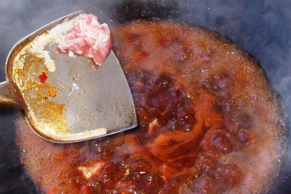 16 - Fleisch in kleinen Grüppchen in die kochende Brühe geben, dabei rühren.jpg